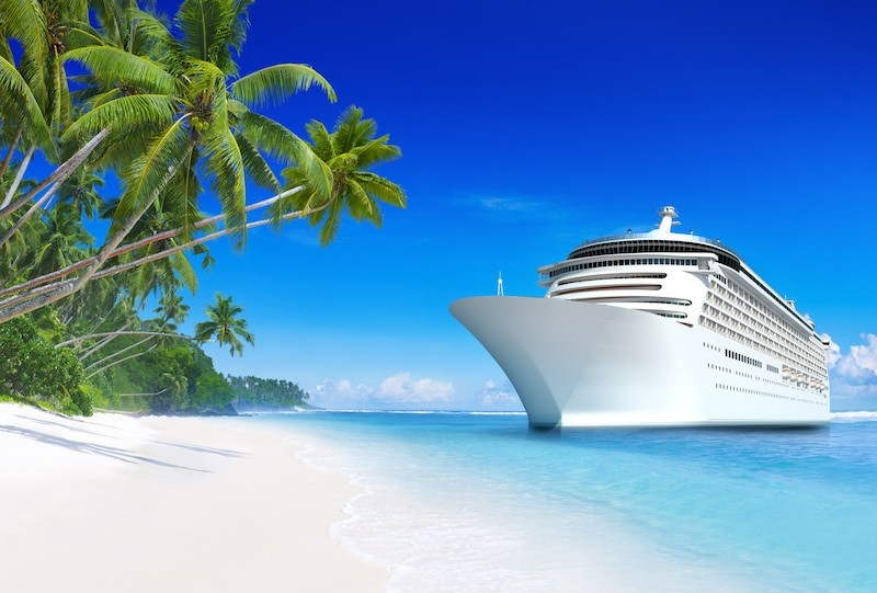 picture of a cruise ship off a white sand beach