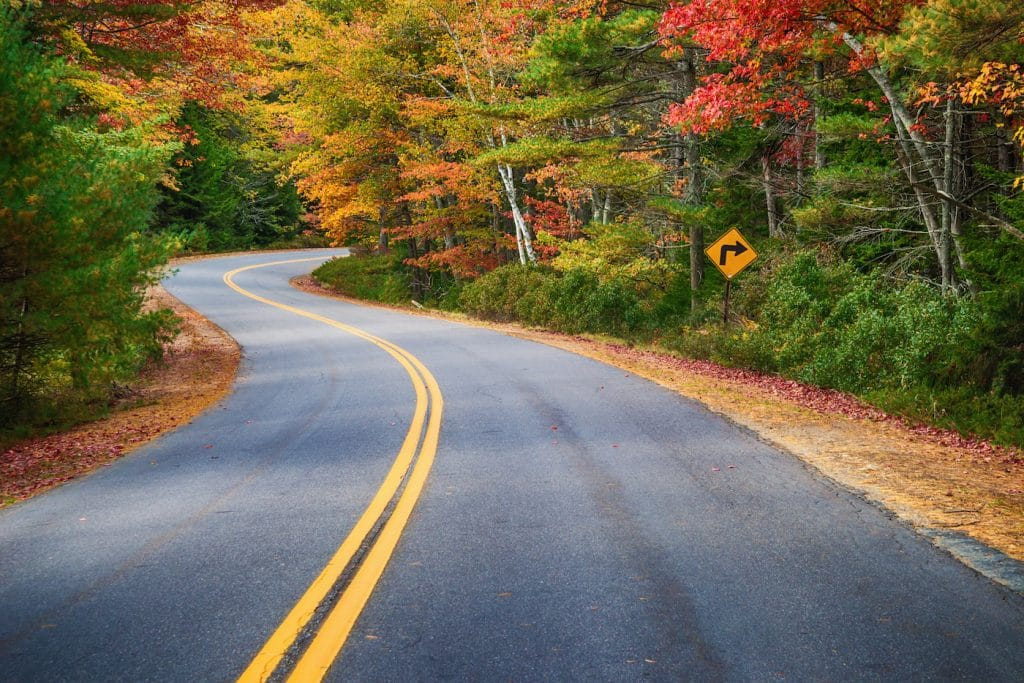 Road Trip through road curves through colorful autumn trees in New England