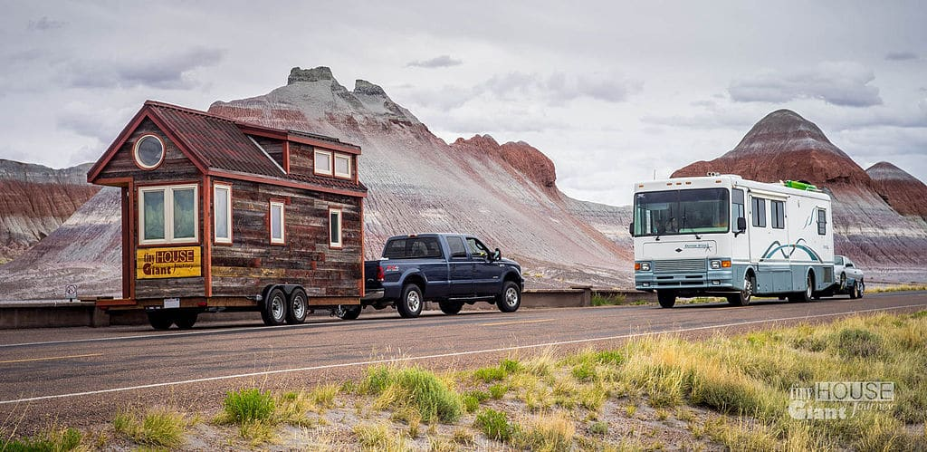 A Tiny house pulled by a pickup truck.