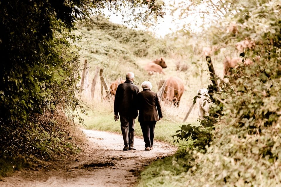 Everything you know about money is wrong: Retired couple walking hand in hand.