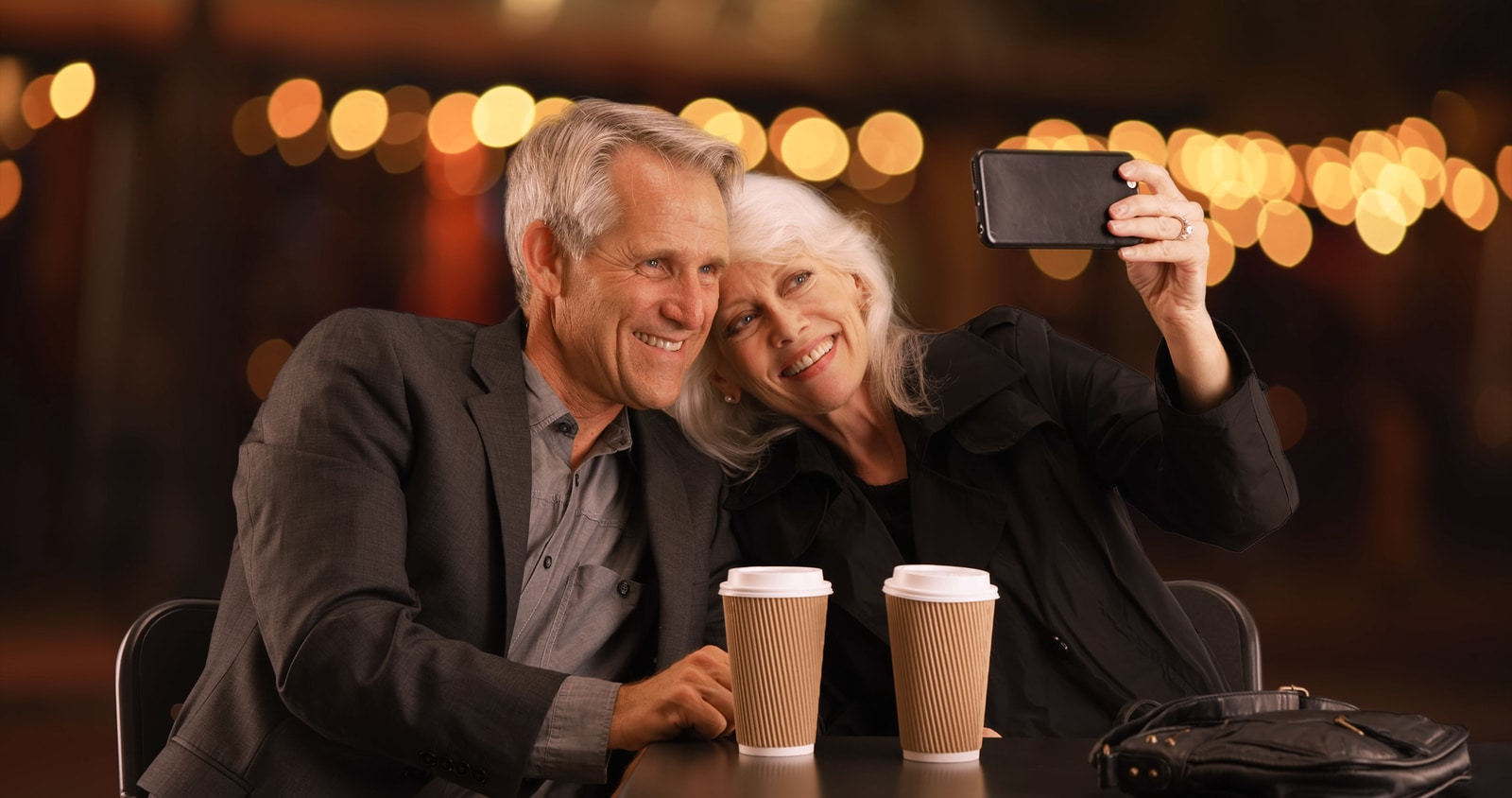 Senior couple out on an evening date taking selfies with smartphone