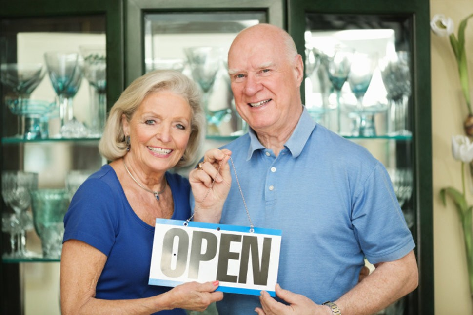 older couple standing with open sign