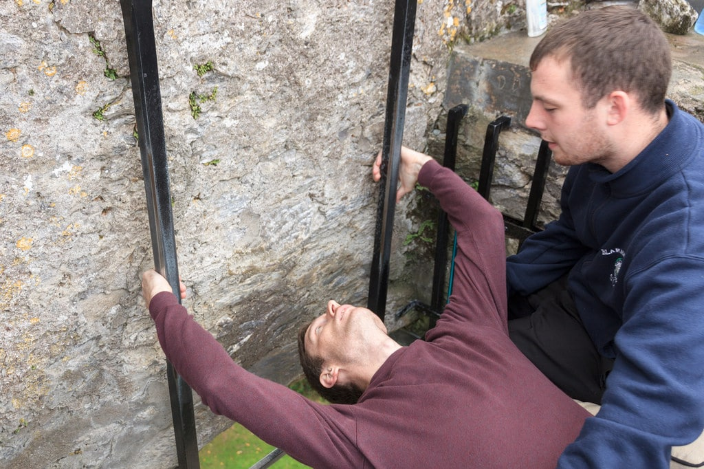 a man trying to backward while holding another man and try to kiss the blarney castle