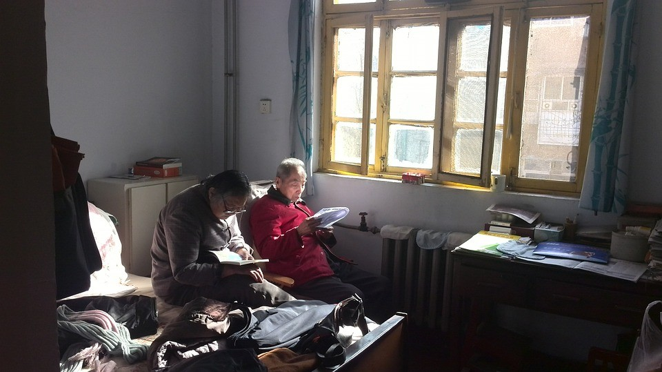 a grandfather and grandmother reading something in the their room