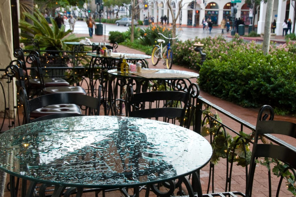 Wrought iron chairs and glass top table setting at sidewalk caf