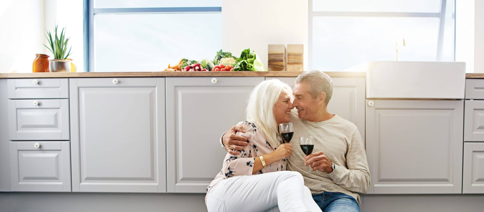 Two elderly people sitting on the kitchen floor with wine glasses, sharing an intimate moment