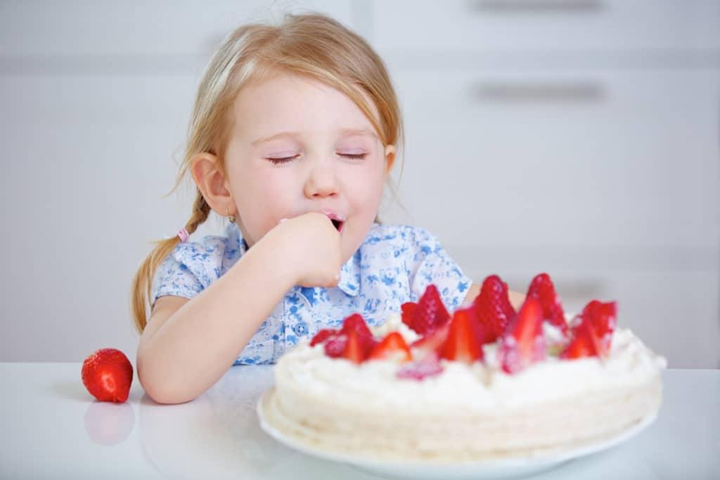 Kind probiert heimlich Sahne von einem frischen Erdbeerkuchen in der Küche