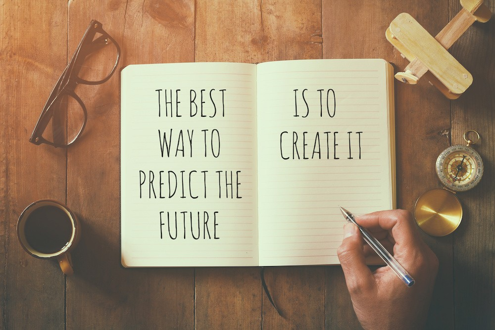 open notebook over wooden table with motivational saying the best way to predict the future is to create it