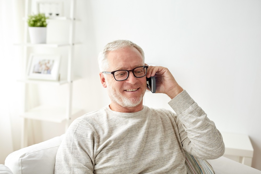 technology, people, lifestyle and communication concept - happy senior man dialing phone number and calling on smartphone at home