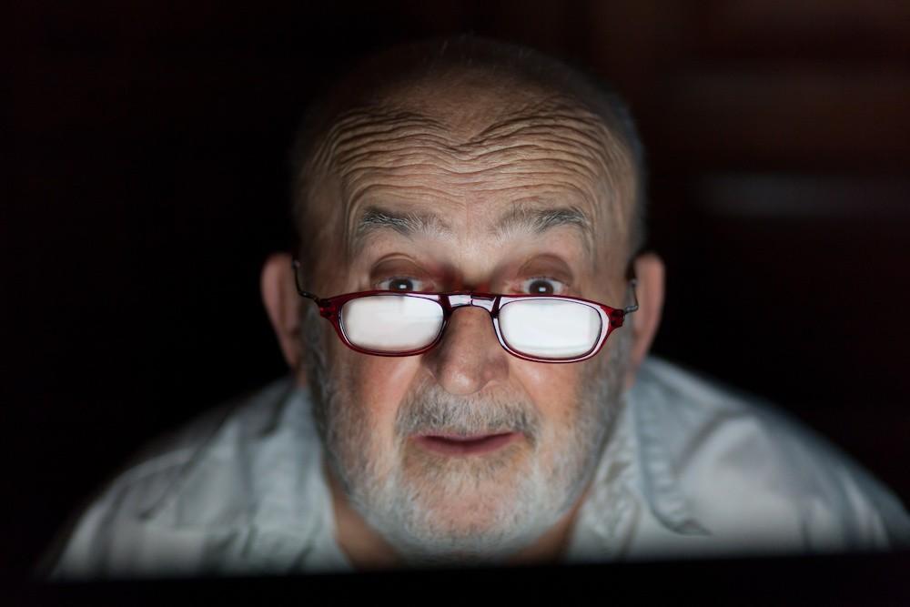 senior man looking at computer screen
