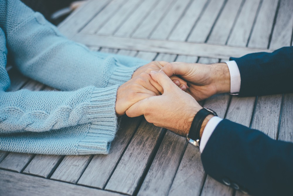 Two persons in love hold their hands on the wooden table, close up image