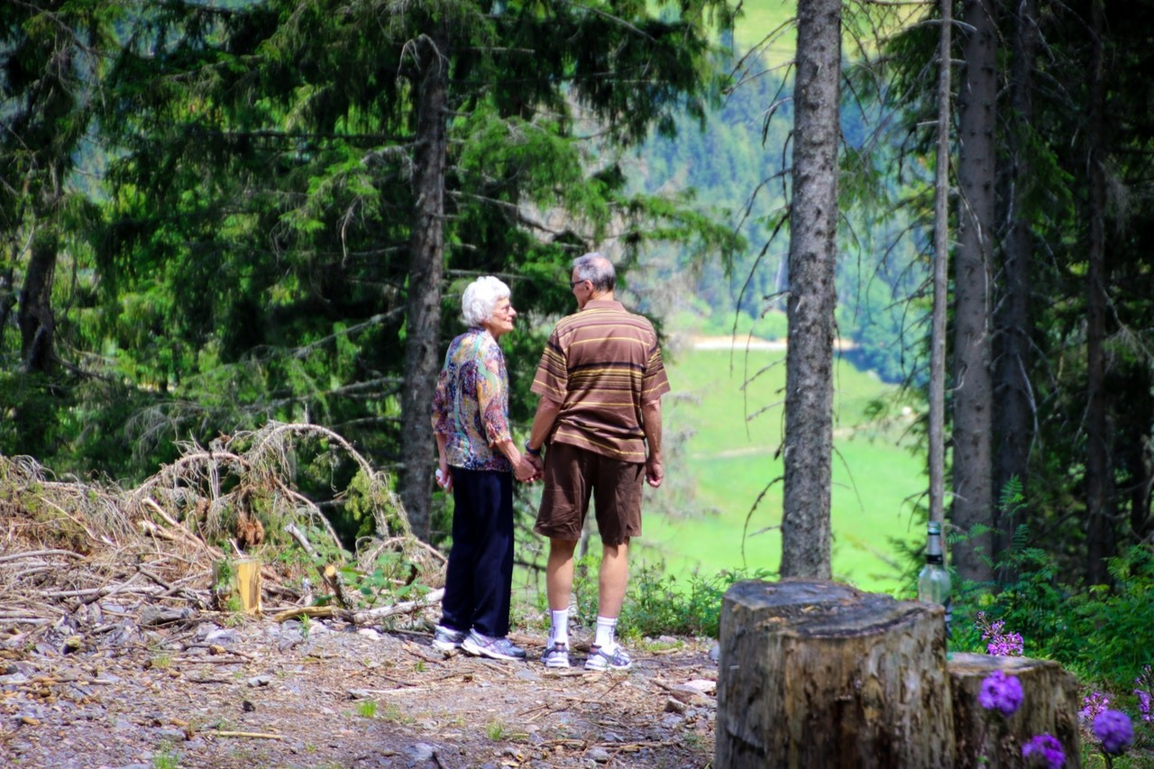 old couple standing in the forest to overcome loneliness at old age